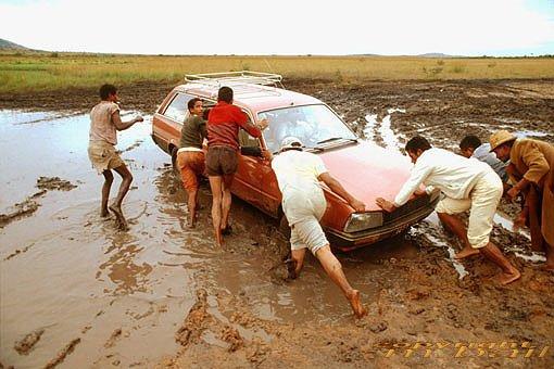 Einige Menschen ziehen ein Auto aus dem Matsch