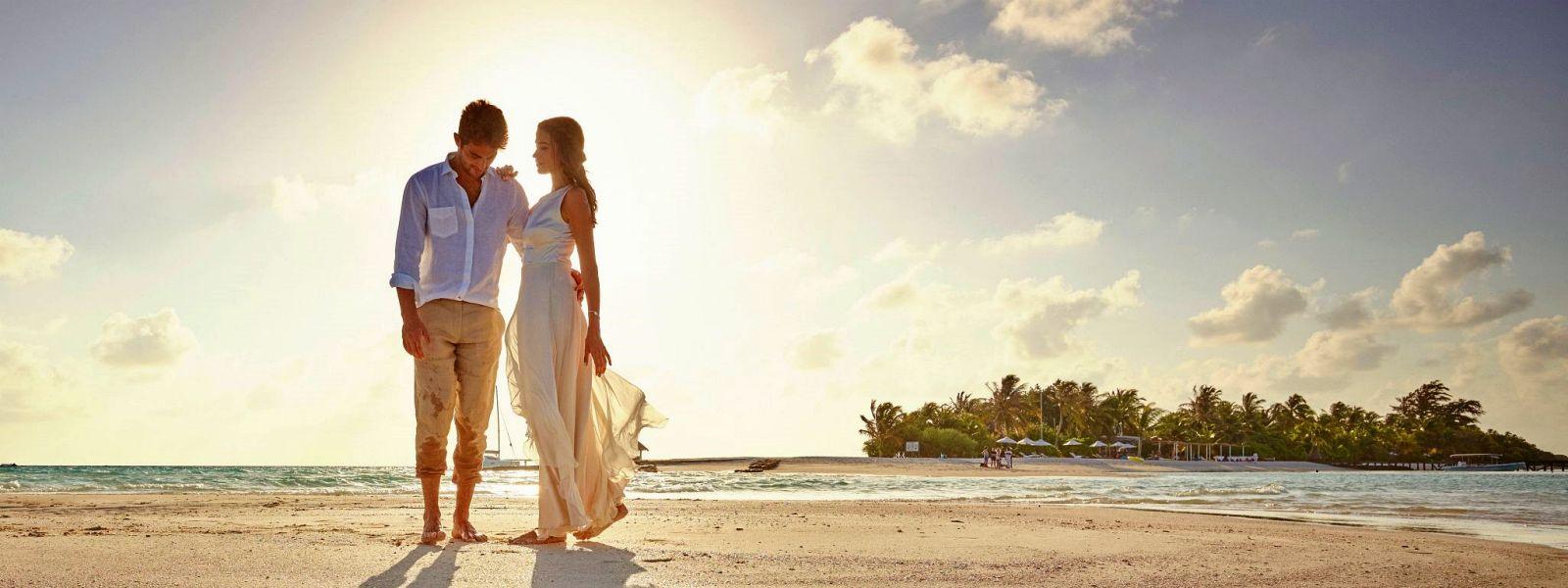 Paar in leichter Brautkleidung auf einer Sandbank auf den Malediven. Kurz bevor die Sonne untergeht