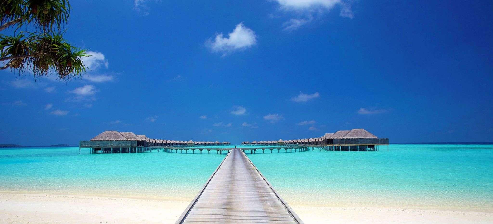 Ein langer Steg vom Strand einer Malediveninsel, mit Wasservillen links und rechts vom Steg