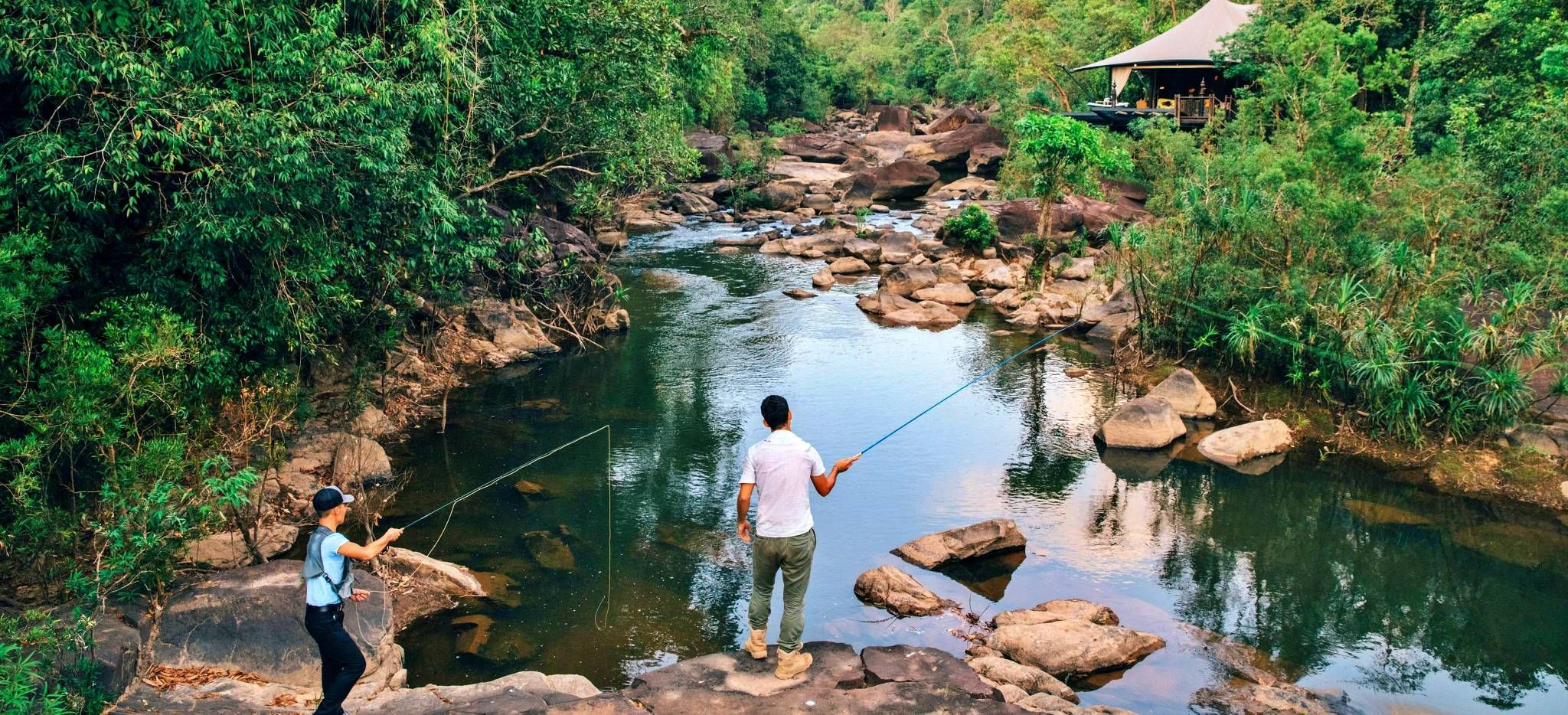 Zwei Männer fischen im Fluss neben einem Zimmer des Hotels Shinta Mani Wild, Kambodscha