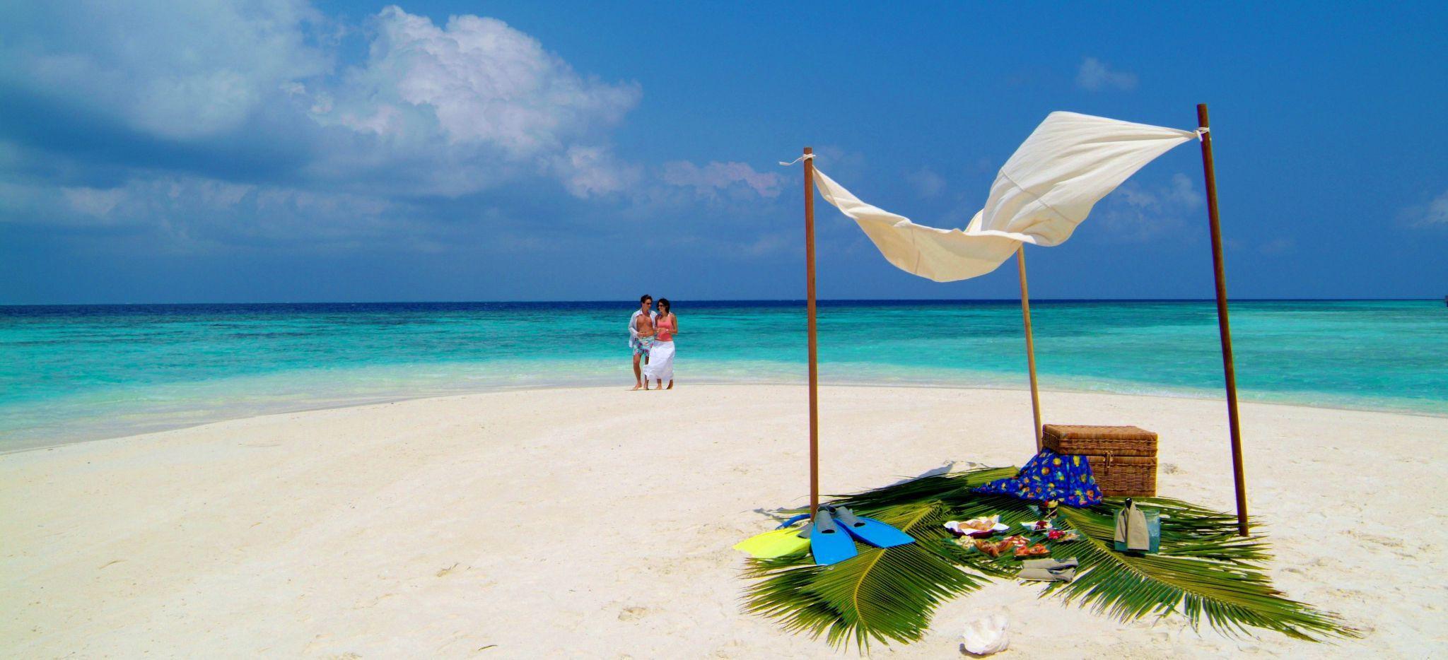 Ein Paar am Strand nahe einem mit einem Sonnensegel geschützten Picknickkorb auf einer Maledivischen Sandbank