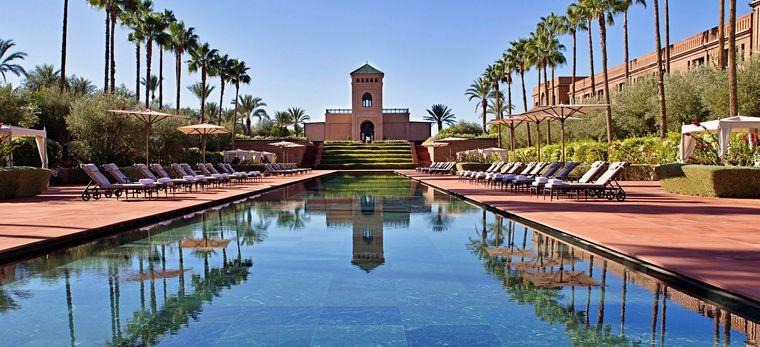 Langer Pool zwischen Palmen vor Marokkanischer Architektur
