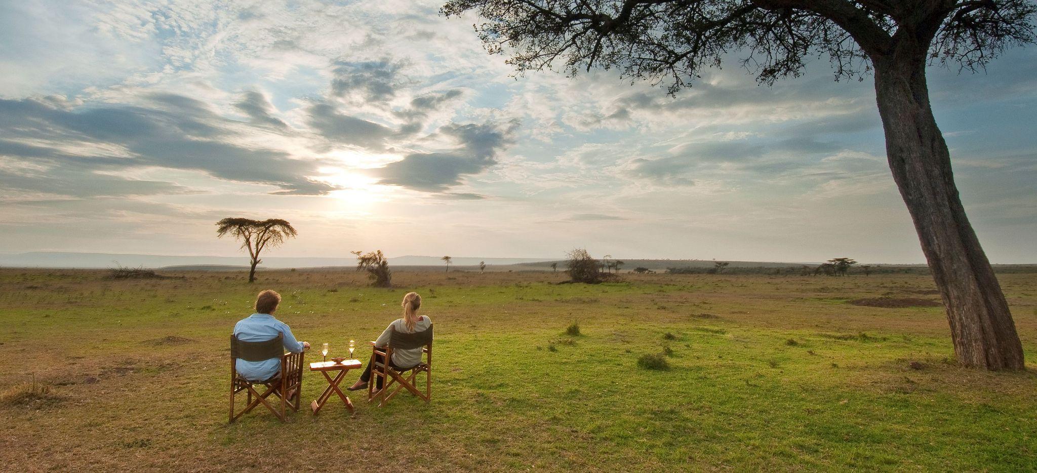 Paar genießt einen Drink mit Blick auf die Tansanianische Savanne
