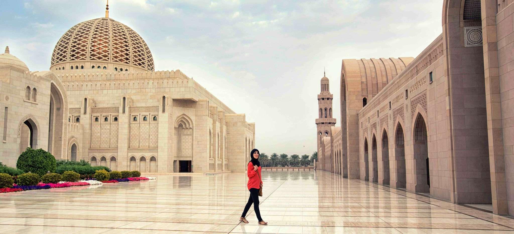 Frau wandert beeindruckt durch die große Moschee von Muskat