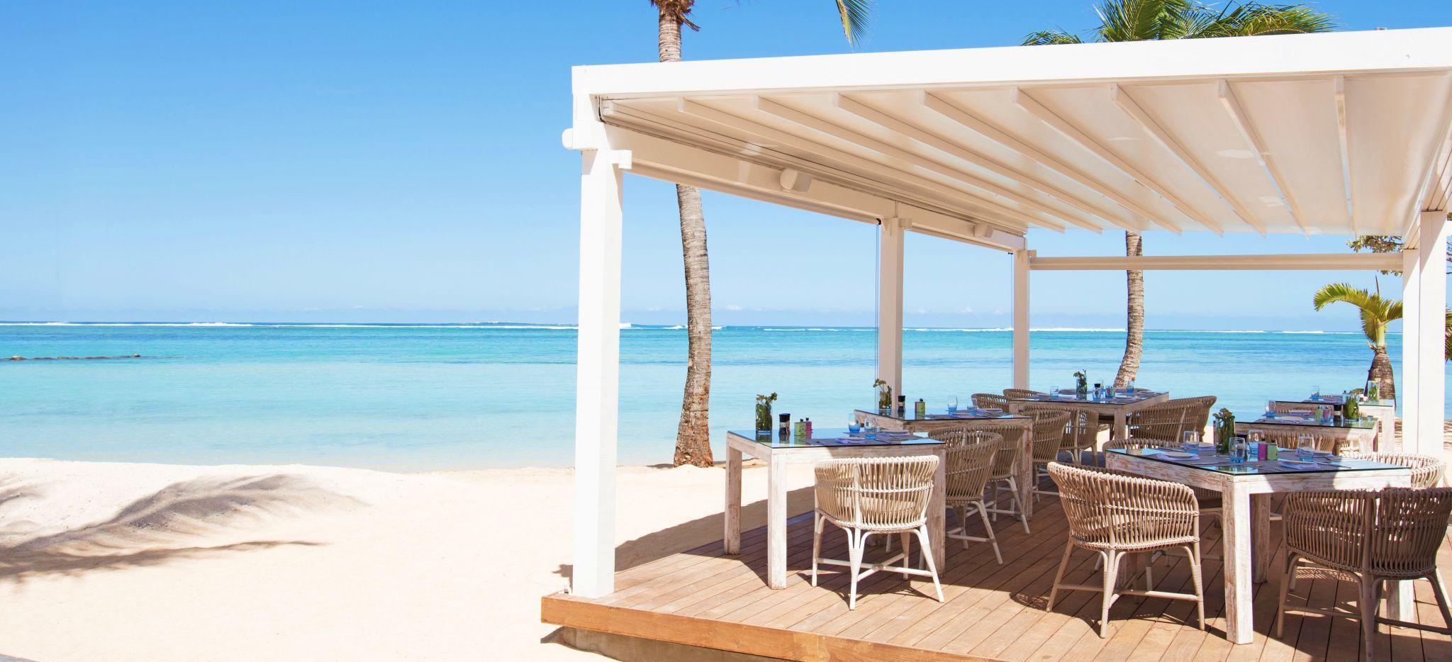 Eine kleine Terrasse am Strand mit gedeckten Restauranttischen