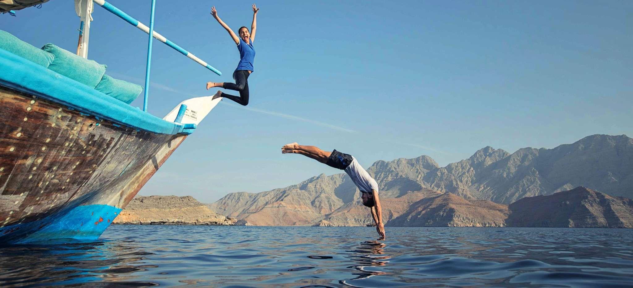 paar springt von einem Boot ins Meer, Nahe Musandam im Oman