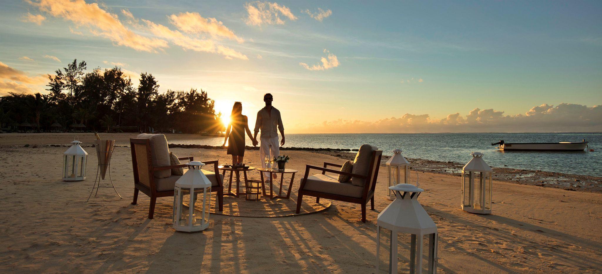 Ein Paar beobachtet den Sonnenuntergang von einer Sitzecke am Strand aus