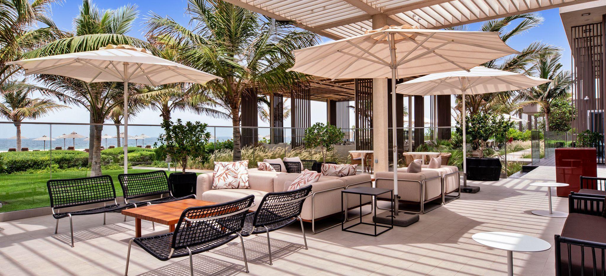 Eine Sonnenterrasse vor Rasen und Strand, die Bar Alfresco im Hotel Oberoi Al Zorah