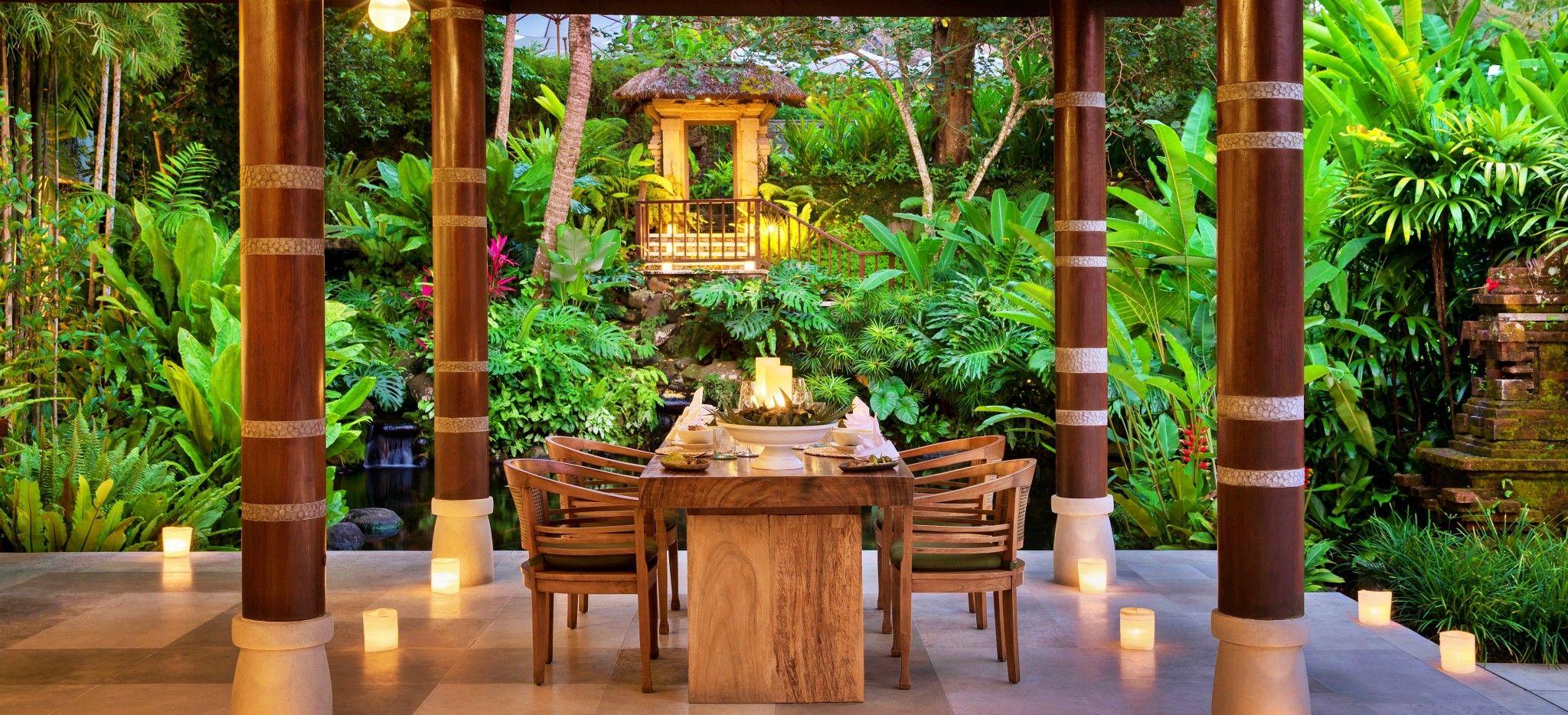 Ein einzelner Esstisch gedeckt für zwei, zwischen großen Säulen mit direktem Blick auf den balinesischen Dschungel