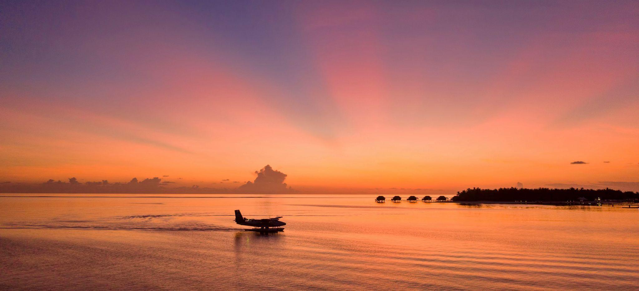 Ein Wasserflugzeug landet im Abendrot vor der Resortinsel Conrad Maldives