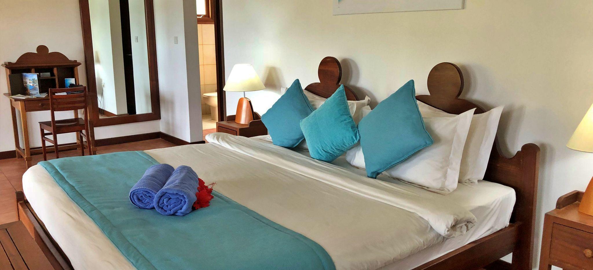 Ein helles Bett umrundet von dunklem Edelholz, Hotelzimmer im L'Archipel auf den Seychellen