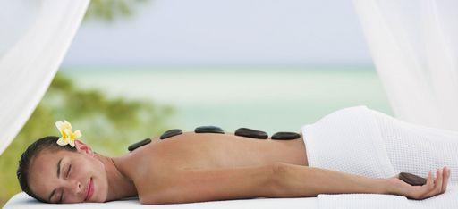 Frau genießt eine Hot Stone Massage mit Blume im Haar, direkt am Strand
