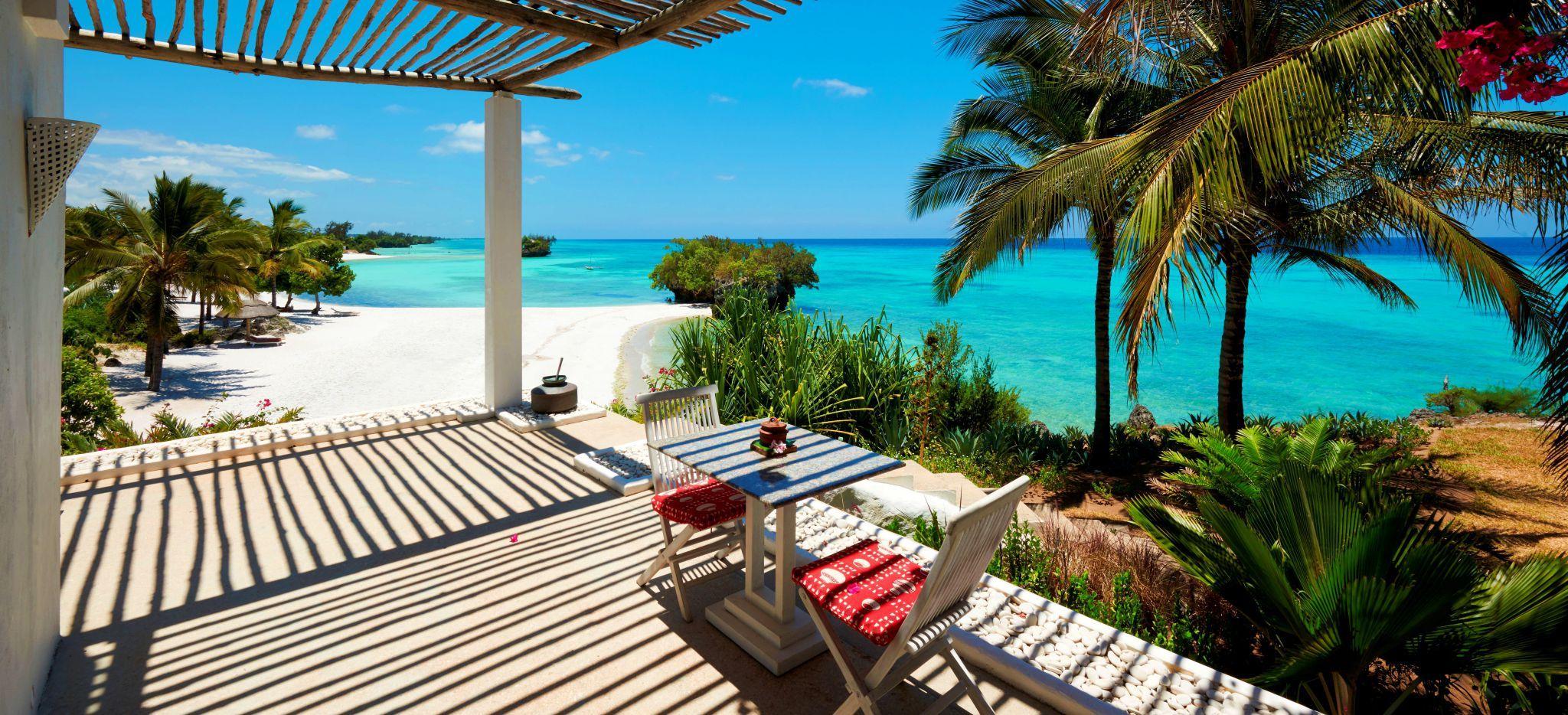 Eine Veranda mit einem kleinen Tisch und Blick auf den Strand und das Meer vor dem Hotel the Aiyana