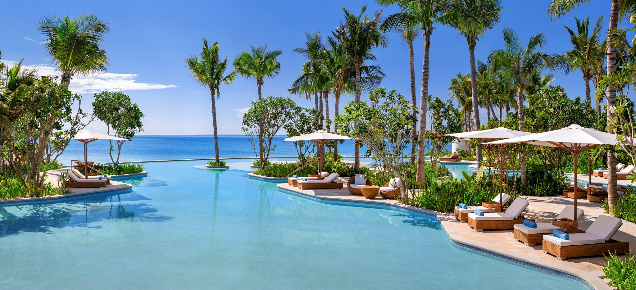 Der Lagoon Pool des Waldorf Astoria Maldives, Palmenumsäumt mit Strandliegen und Sonnenschirmen