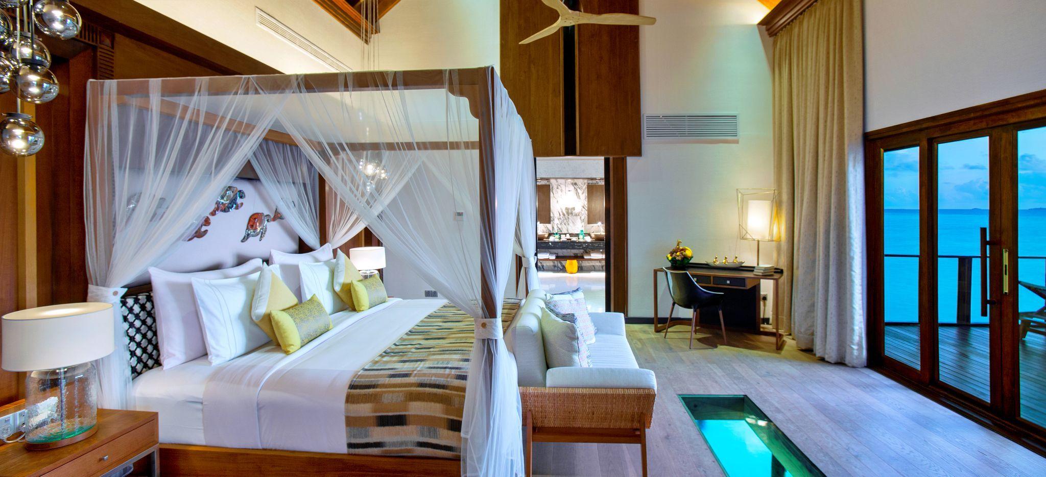 Ein geräumiges Schlafzimmer mit Himmelbett in einer Wasservilla des Hotels OZEN auf den Malediven
