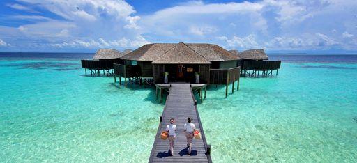 """Zwei Masseurinnen laufen über einen Steg zum auf Stelzen in die Lagune gebautem Spa des Hotels """"Lily Beach"""""""