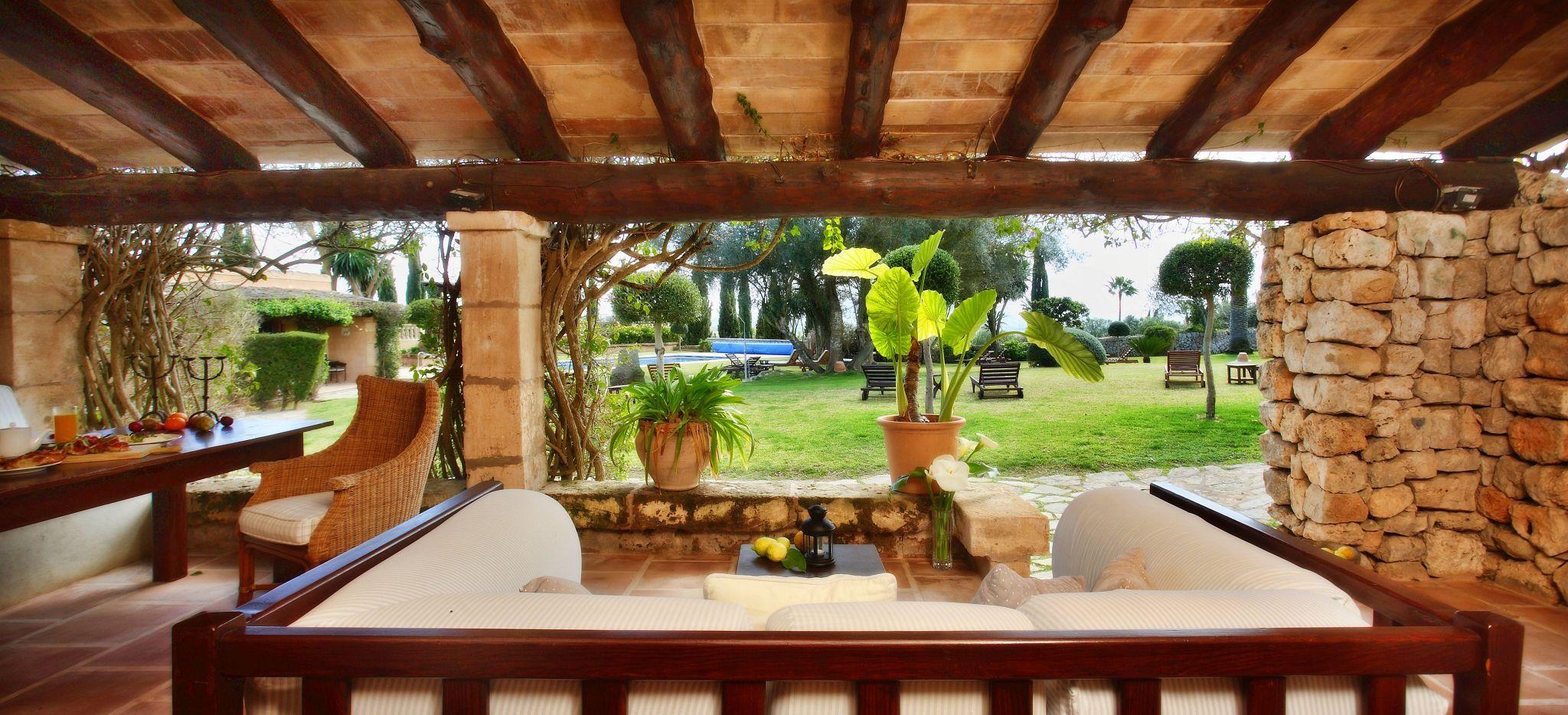 Eine Terrasse mit einer gemütlichen Couch und Blick auf einen mediterranen Garten