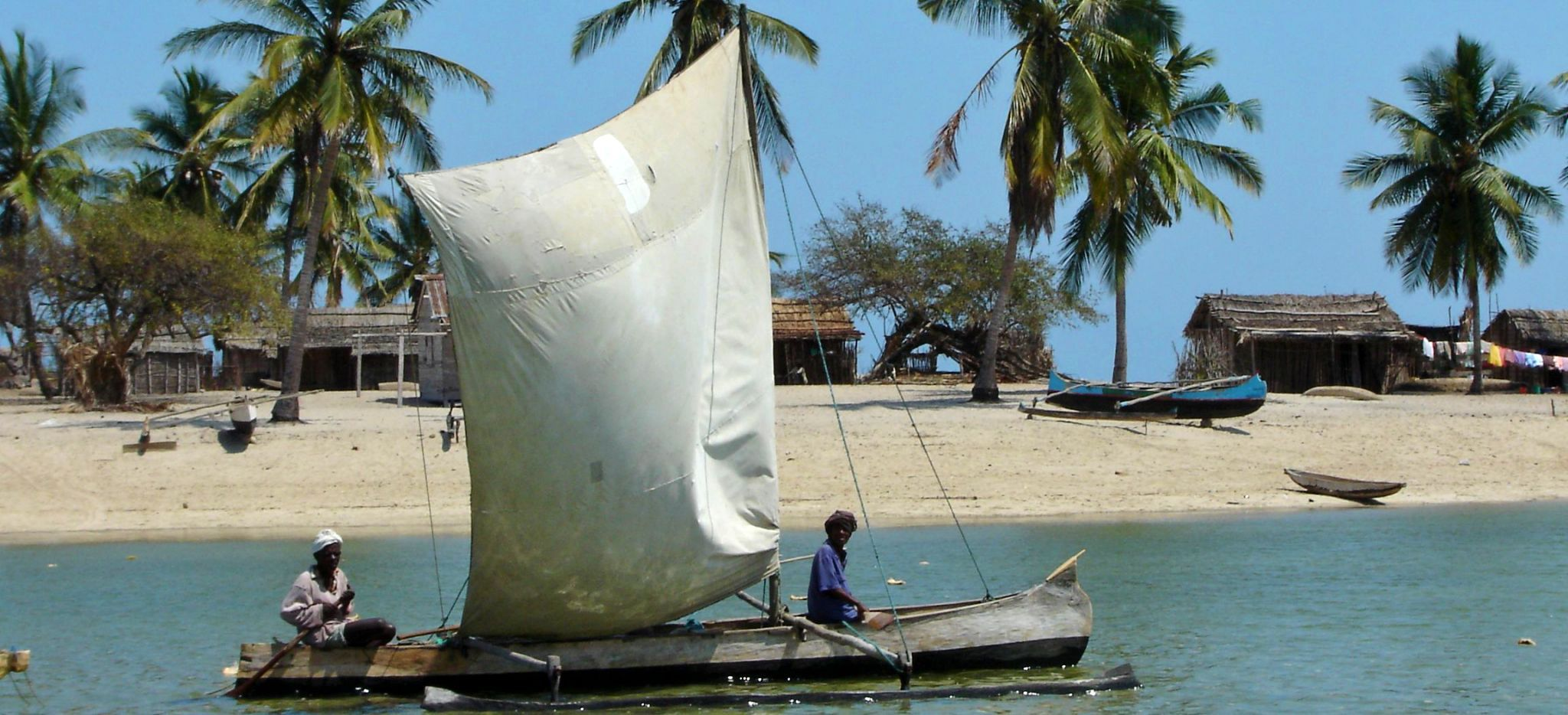 Zwei Männer auf einem traditionellen Segelboot vor Madagaskar fahren an einem Strand vorbei