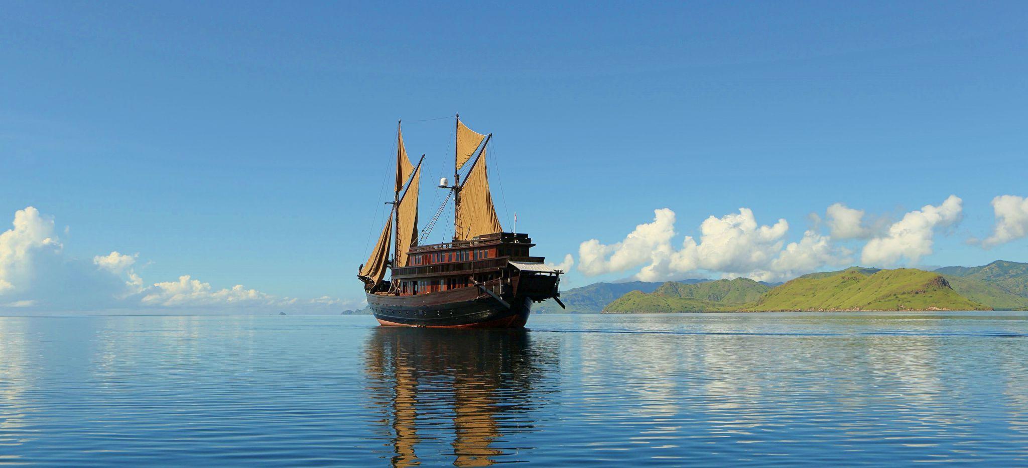 """Die Yacht """"Alila Purnama"""" auf dem Meer, mit Inseln im Hintergrund"""