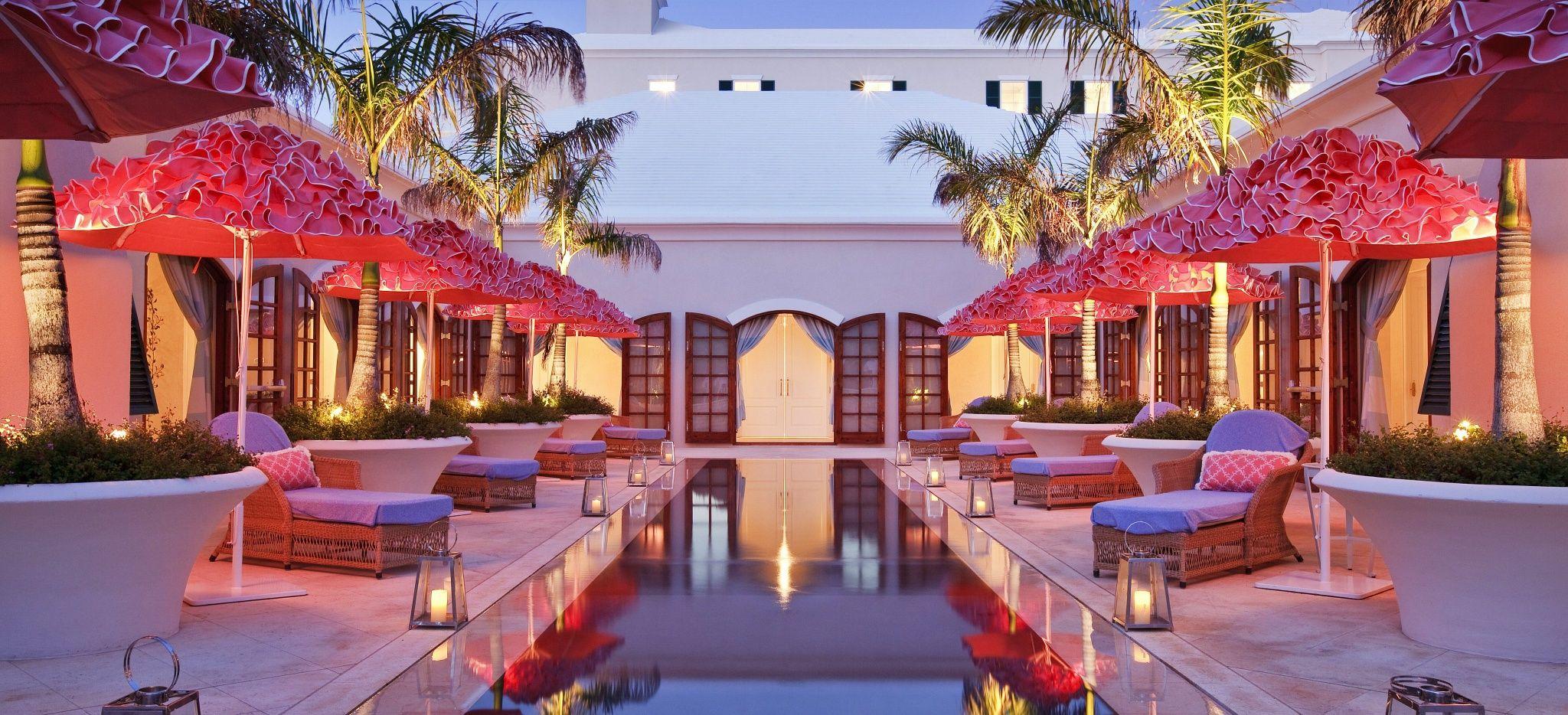 """Einige rosane Sonnenschirme und Strandliegen um einen kleinen Pool im Wellnessbereich des """"Rosewood Tucker's Point"""" Hotels"""