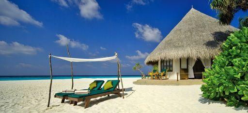Eine Strandvilla mit einer Strandliege auf der Malediveninsel Coco Palm Dhuni Kolhu