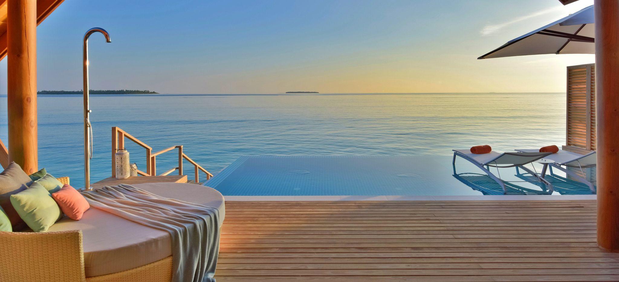 Terrasse eines Overwater-Bungalow im Hotel Faarufushi Maldives, auf den Malediven. Privater Pool mit Sonnestühlen, Holzterrasse und das Meer mit Sonnenuntergang