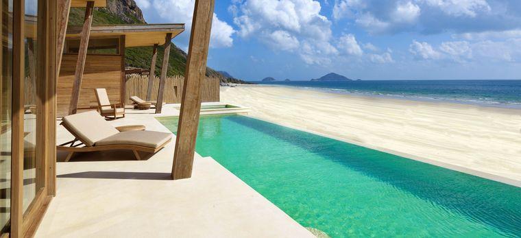 Die Terrasse einer Villa mit einem langem privaten Pool direkt am Strand