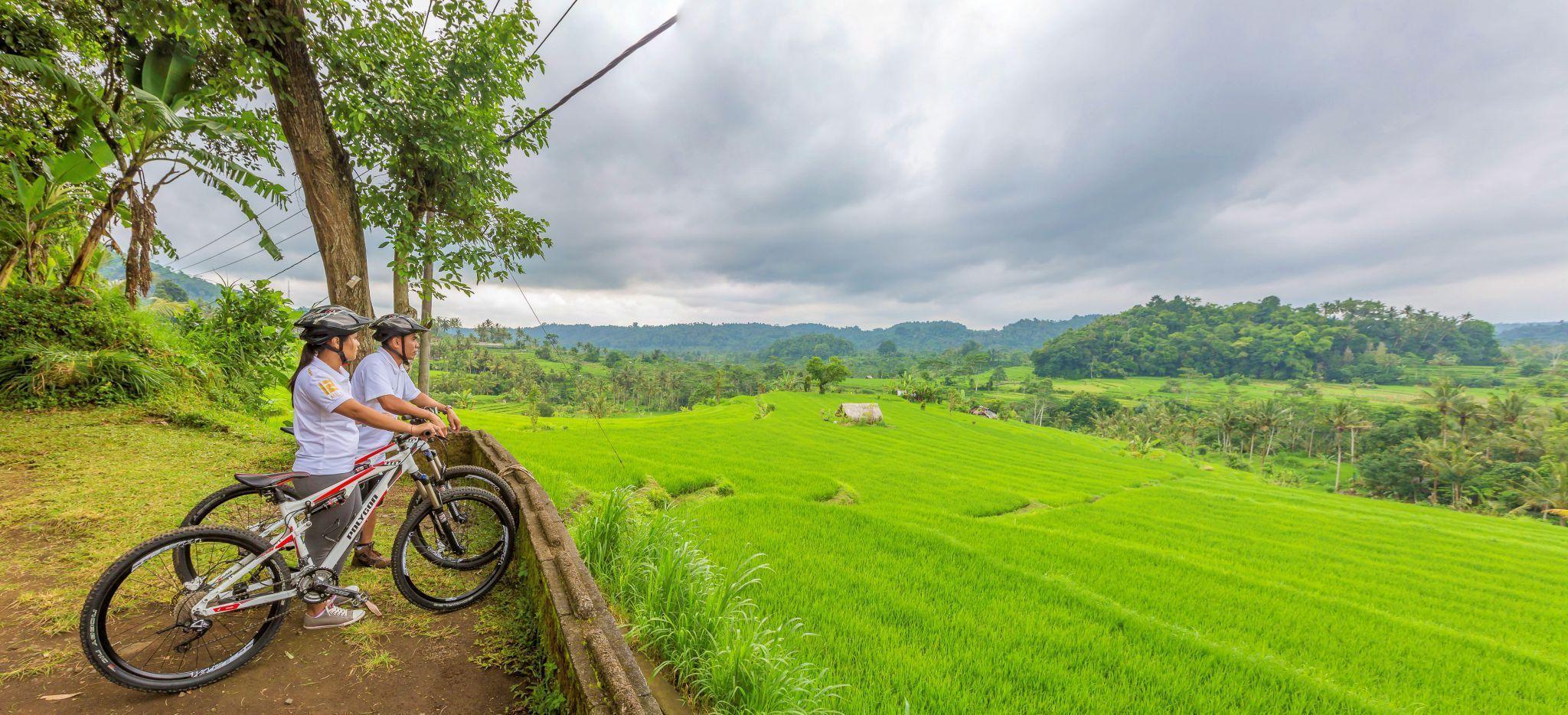 Paar blickt von den Bergen Balis von einem Berg runter auf das Meer