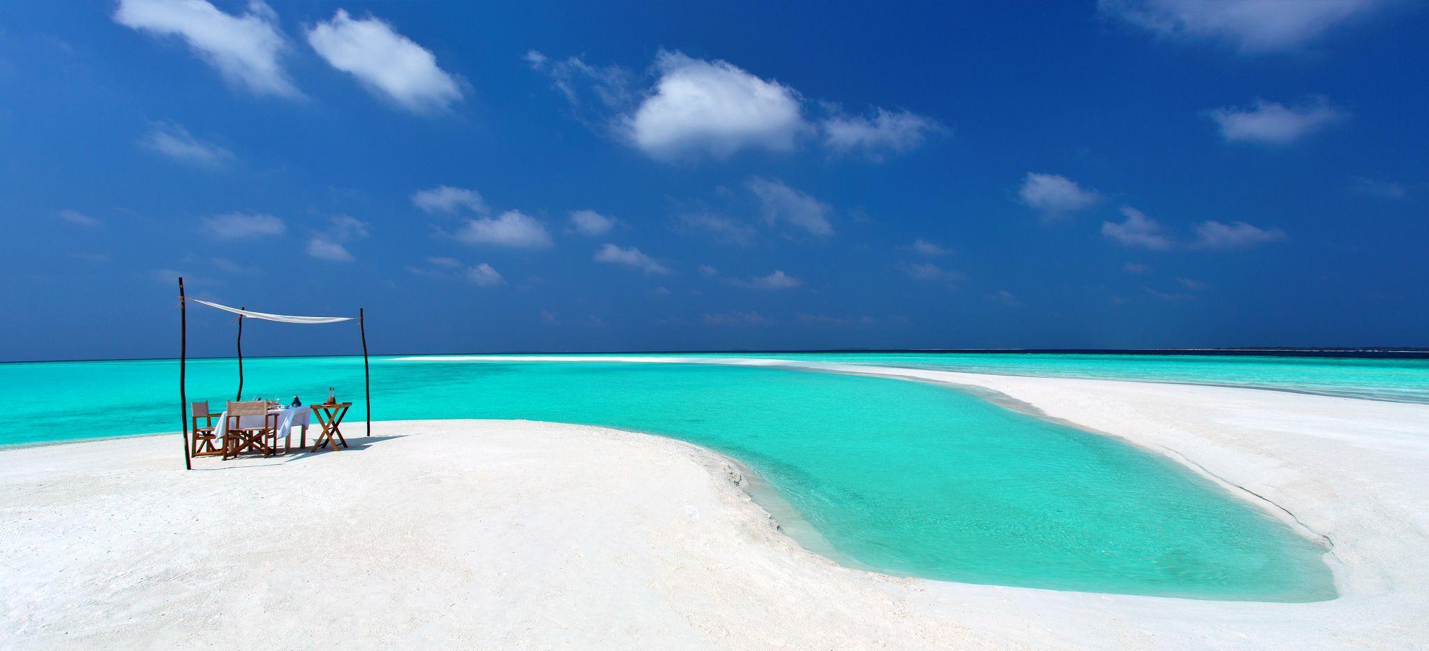 Ein Picknick auf einer Sandbank der Malediven vorbereitet, das Meer darum ist hell türkisblau