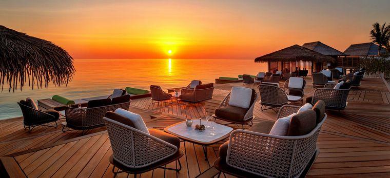Sonnenuntergang hinter einer Über-Wasser Terasse mit Kaffeetischen des Waldorf Astoria Maldives