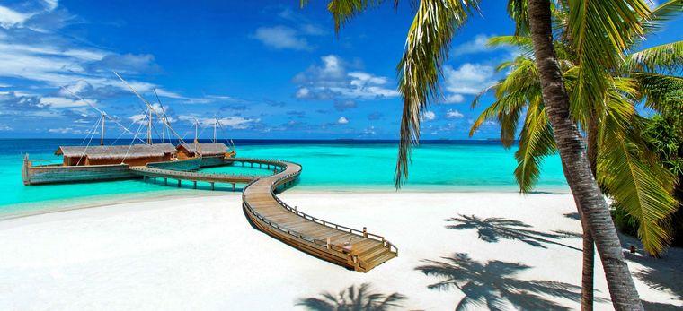 Ein weißer Sandstrand mit einem Steg, an dem ein Restaurant liegt, das aussieht wie die traditionellen Dhonis der Malediver