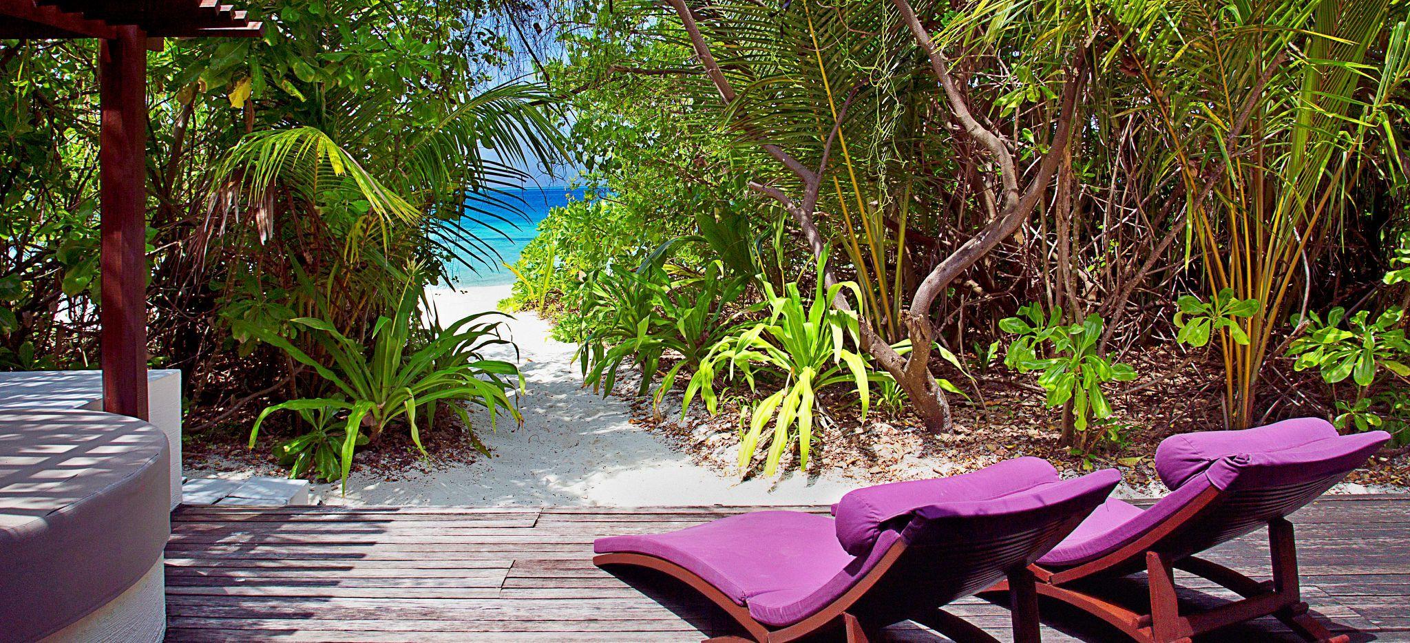 Blick auf das Meer zwischen Büschen von der Terrasse eines Hotelzimmers im Hotel Coco Palm Bofu Hithi auf den Malediven