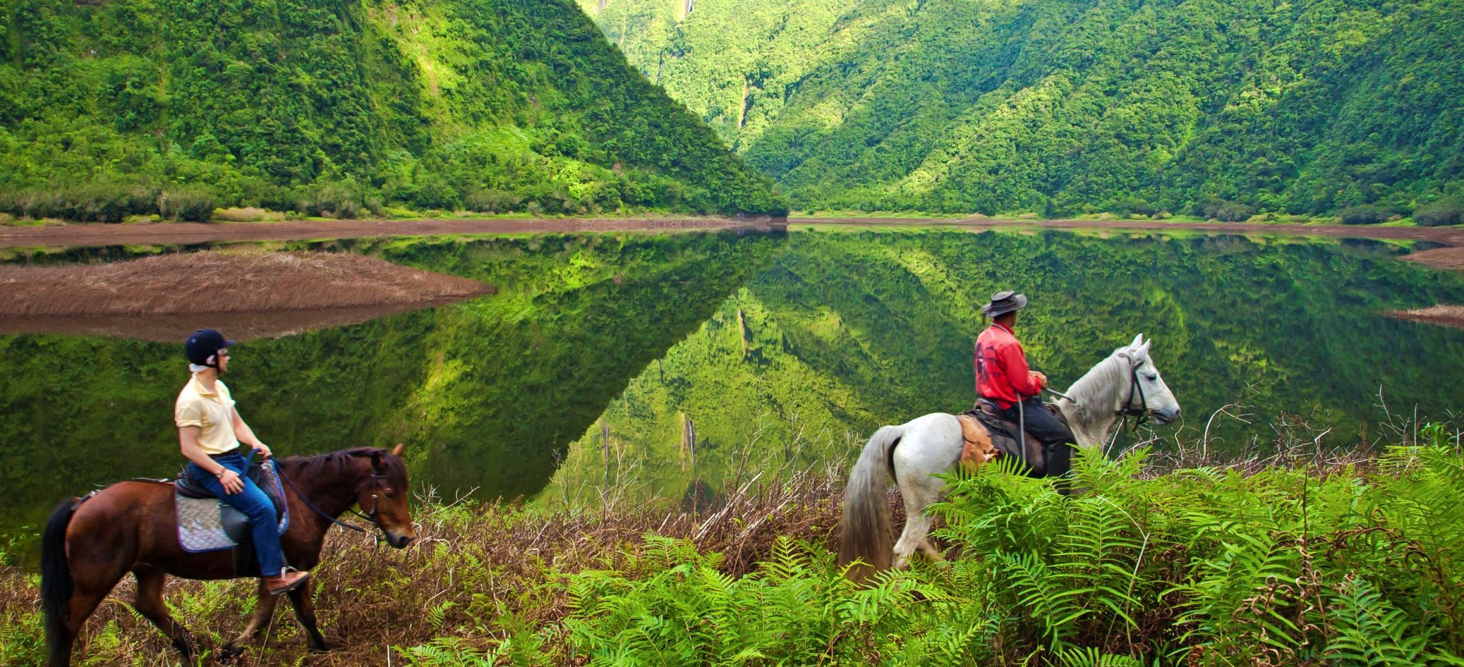 Zwei Reiter neben einem Bergsee auf der Insel La Réunion