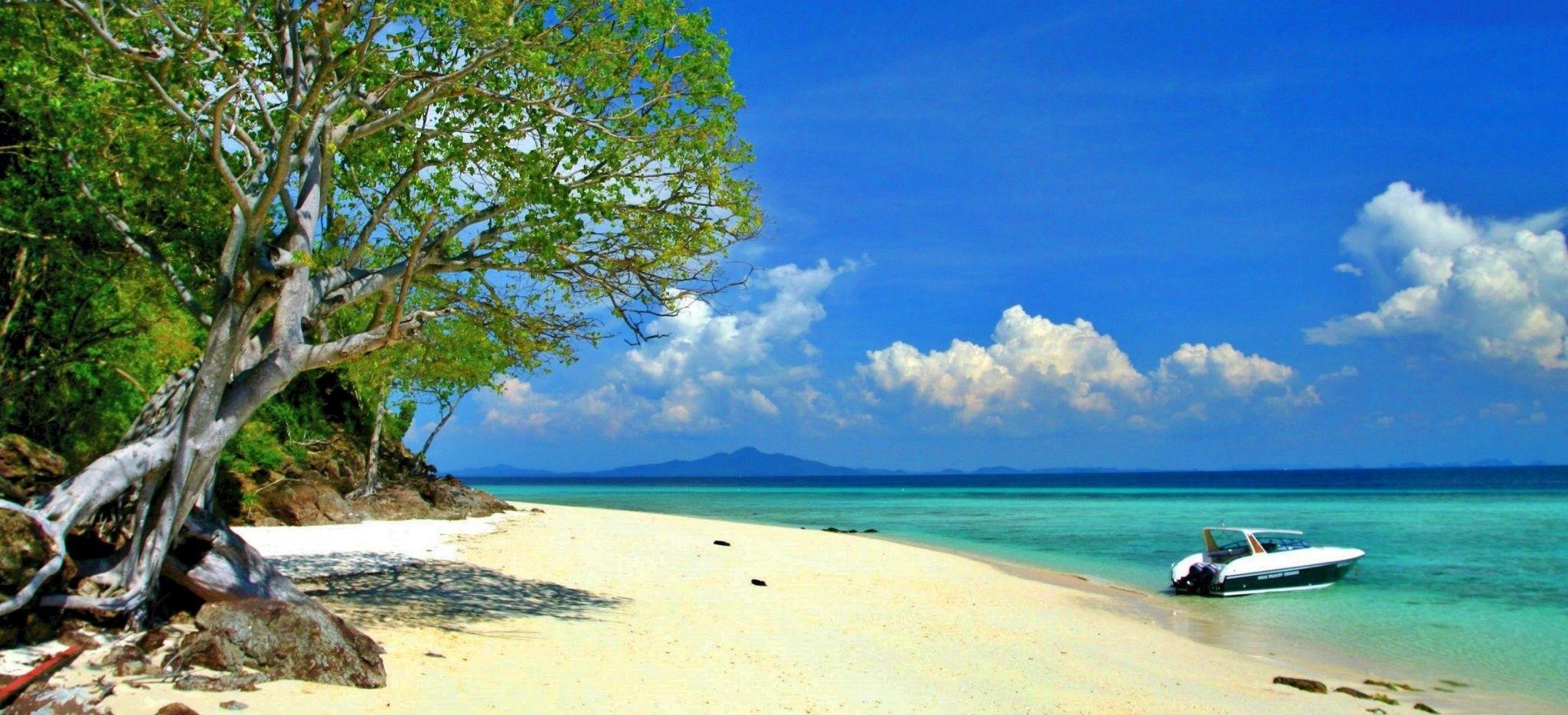 Ein verlassener Strand direkt zwischen Dschungel und Meer. Im Wasser liegt ein Schnellboot.