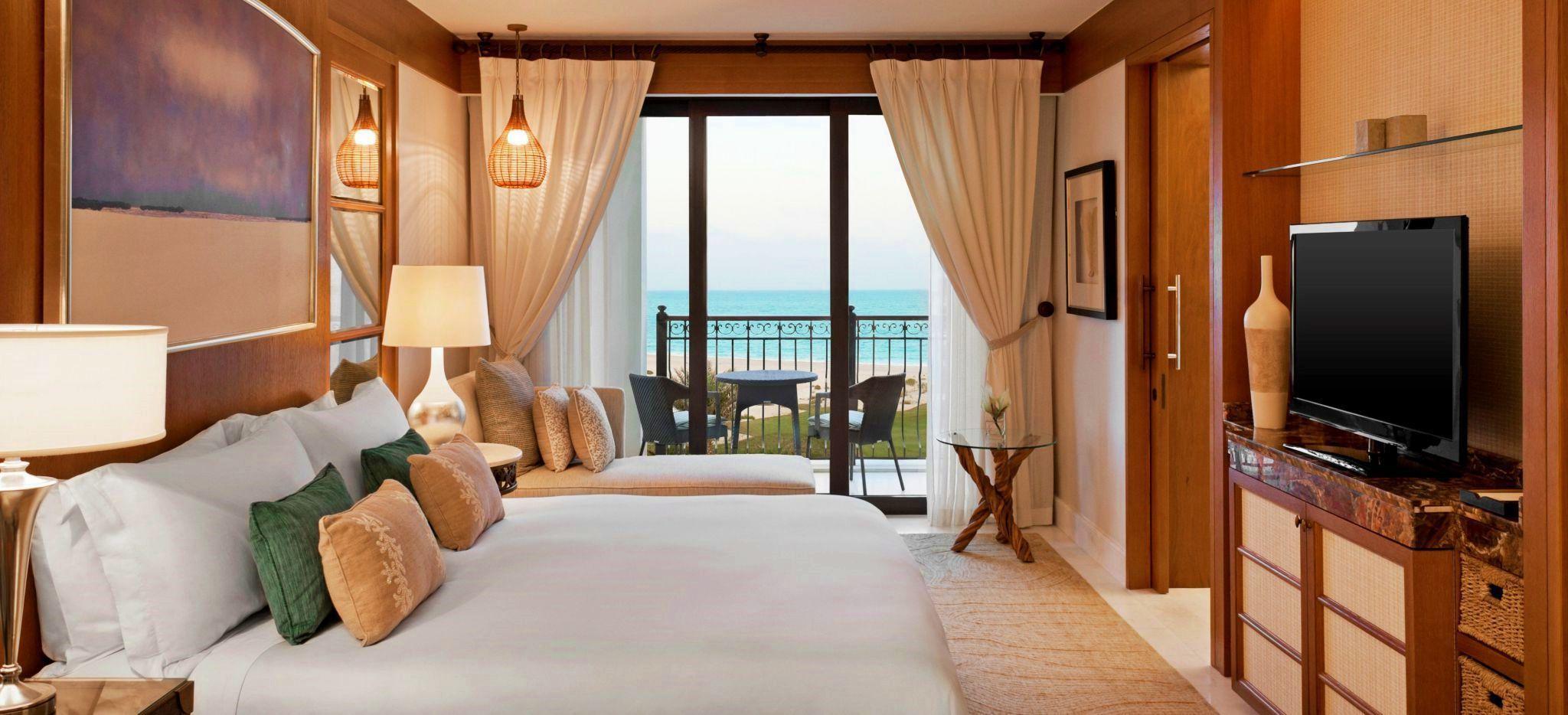 Blick auf das Hotelzimmer (Superior Room) des St. Regis Saadiyat Island. Luxuriöse Einrichtung, King Size Bett, Blick auf das Meer.