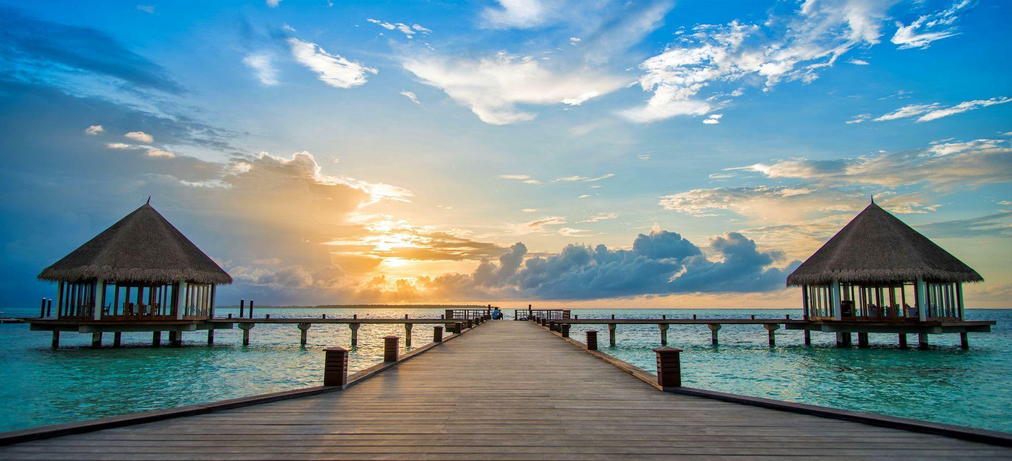 Ein langer Steg mit Zwei Gebäuden, vor dem Sonnuntergang über einer Malediven-Insel