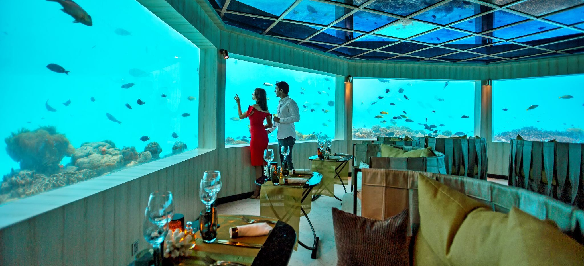 Ein paar betrachtet Fische durch ein Fenster in einem Unterwasser Restaurant im Hotel OZEN, Malediven