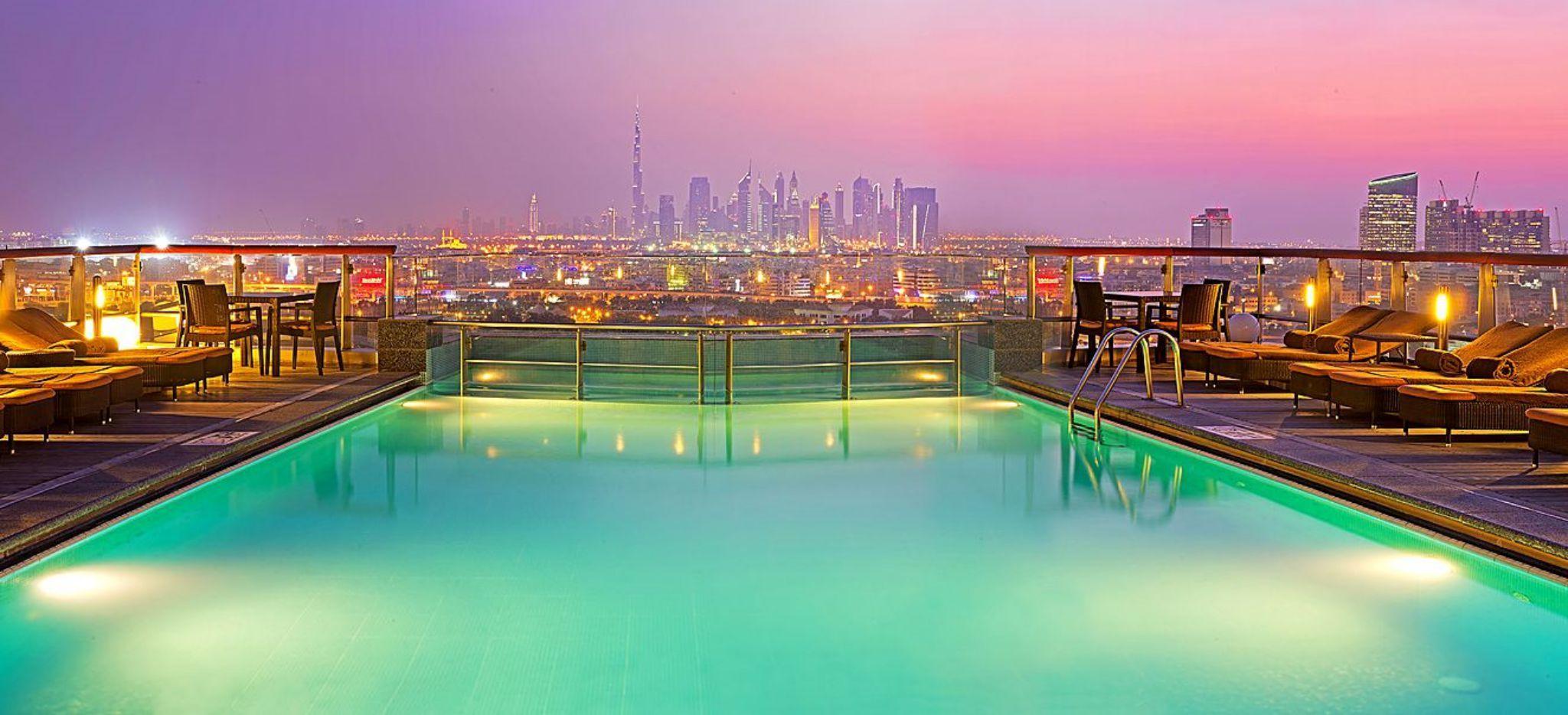 """Pool des Hotels """"Hilton Dubai Creek"""" auf die Skyline Dubais. Hell erleichtet"""