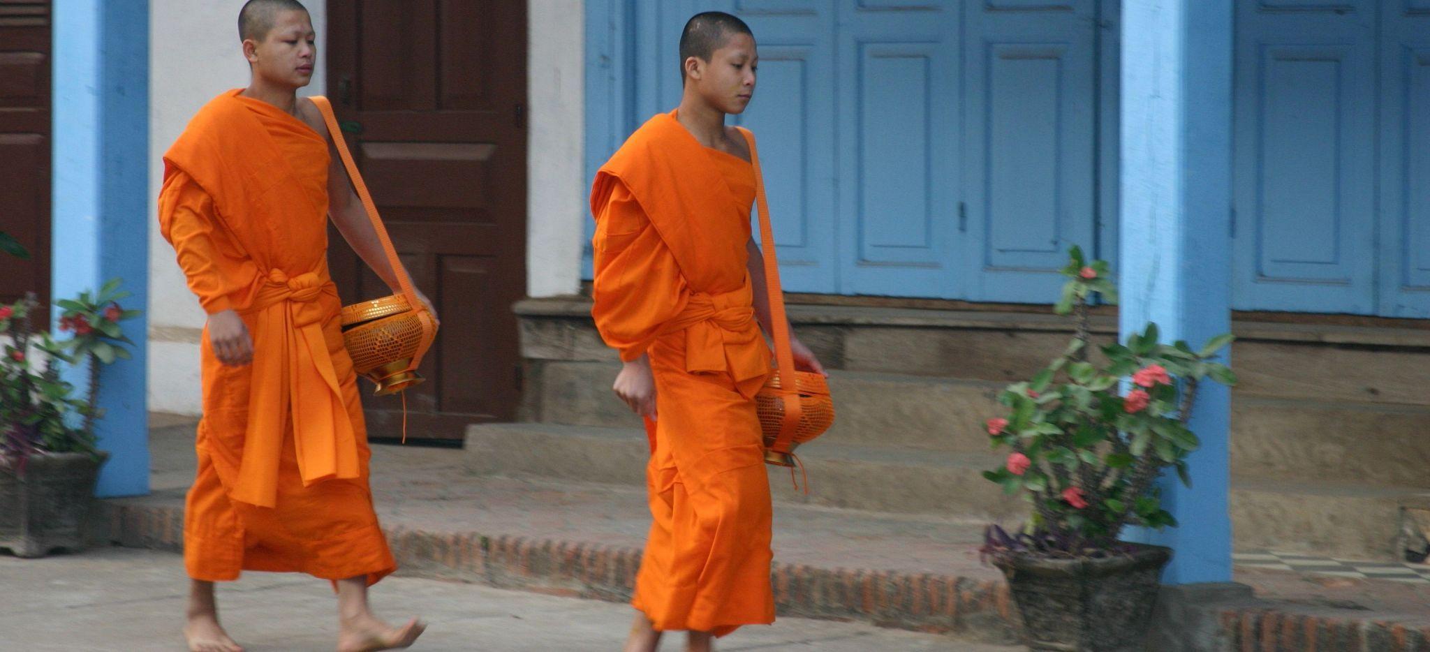 Zwei junge Buddhistische Mönche schreiten an einem blauen Haus vorbei, Laos