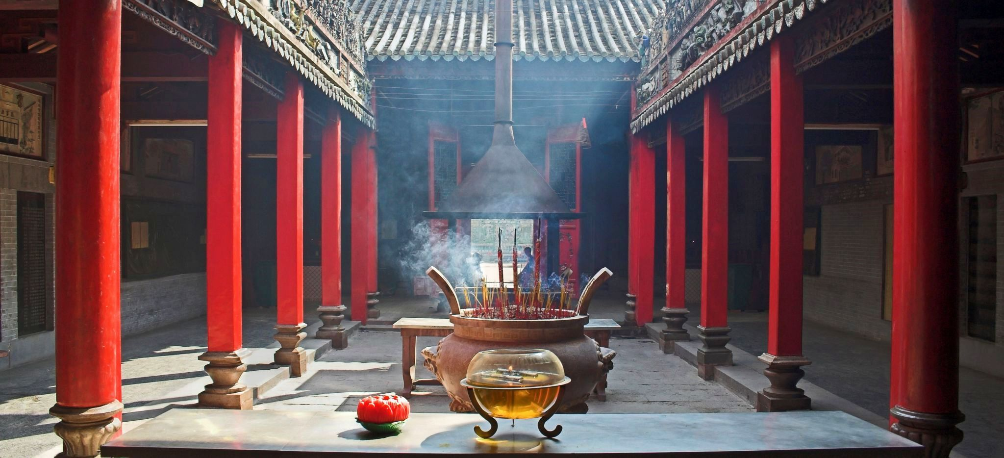 Tempel mit roten Säulen, druchflutet vom Rauch von Räucherstäbchen