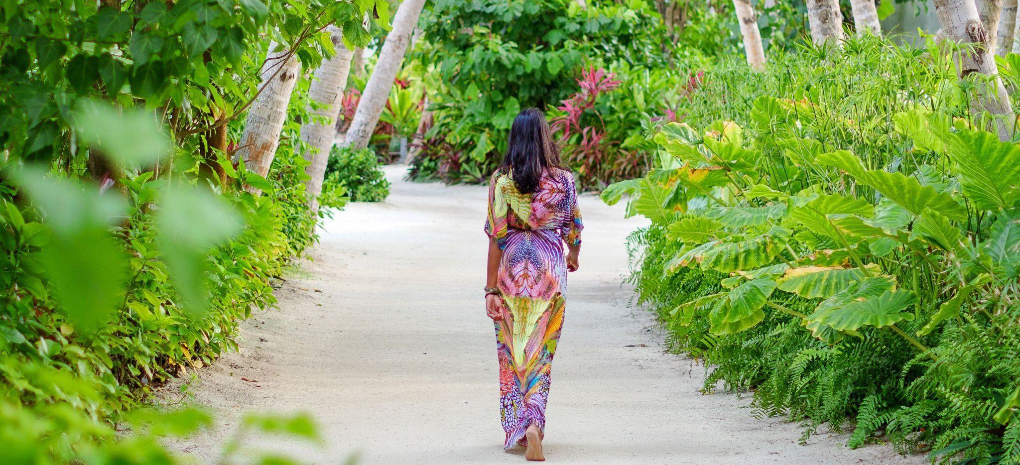 Eine Dame in einem Bunten Kleid läuft durch einen gepflegten Dschungelweg
