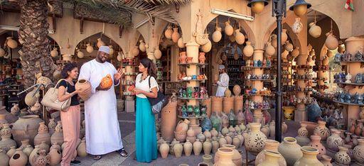 Zwei Touristinnen verhandeln mit einem Mann in traditioneller Kleidung auf dem Basar von Nizwa, Oman