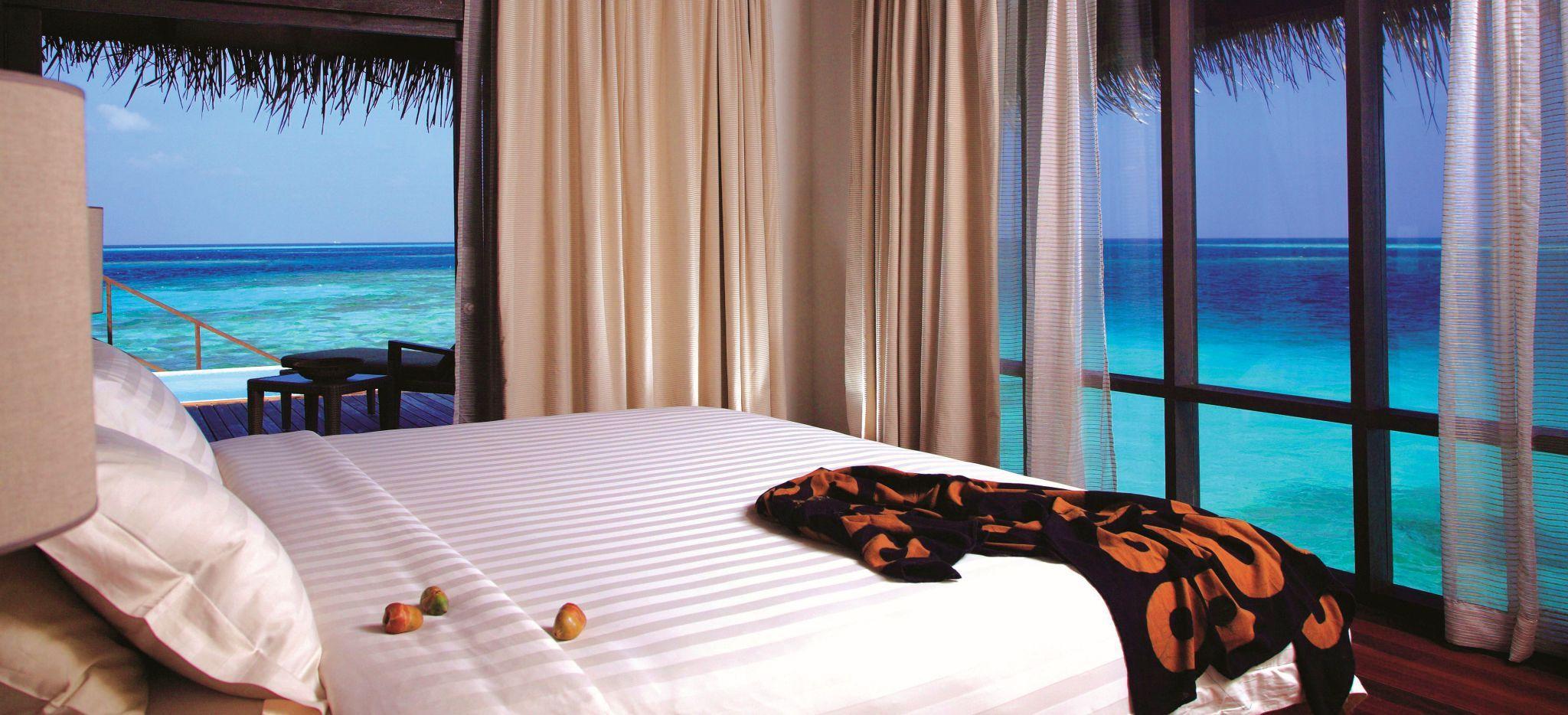 Ein Schlafzimmer mit Blick auf die türkise Lagune der Malediveninsel Coco Palm Bodu Hithi