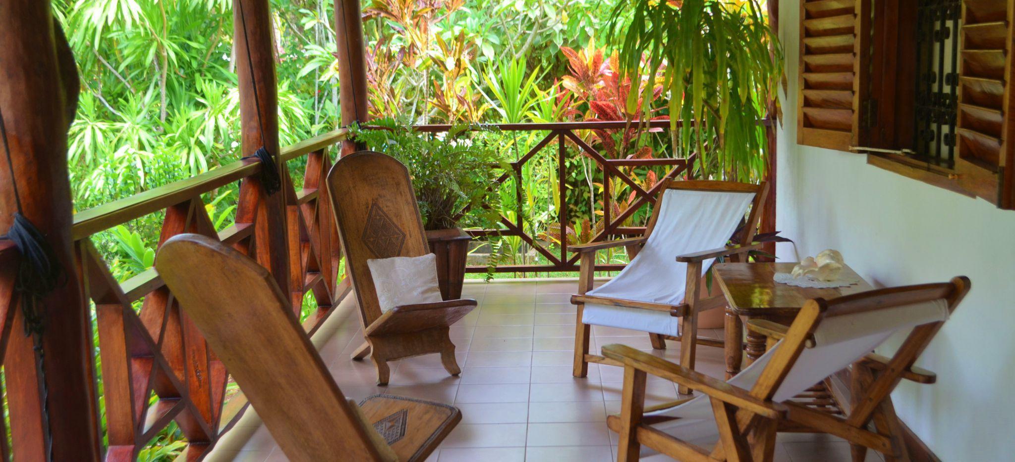 Sitzecke auf einer Kolonialen Terrasse vor einem tropischen Garten auf den Seychellen, im Gästehaus Villa Bambou