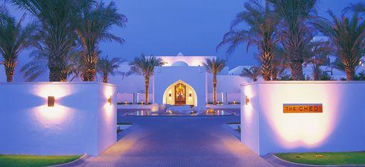 """Eingang in das Hotel """"The Chedi Muscat"""" mit Dattelbäumen und weißen Mauern, Nachtaufnahme"""