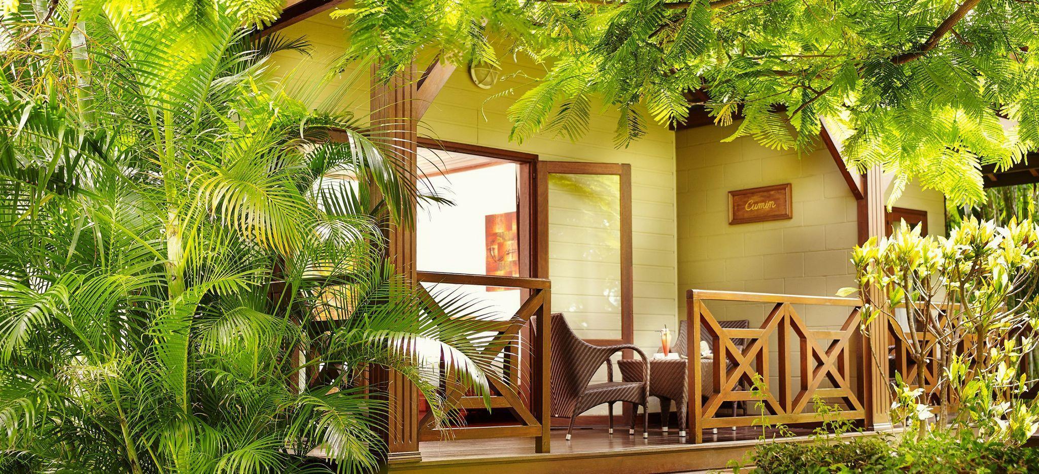 Ein Hotelzimmer eingerahmt von tropischem Gewächs
