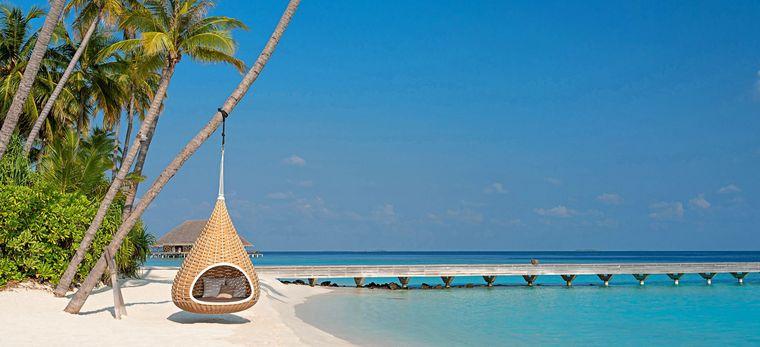 Hängestuhl an einer Palme am Strand des Hotel Velaa Private Island