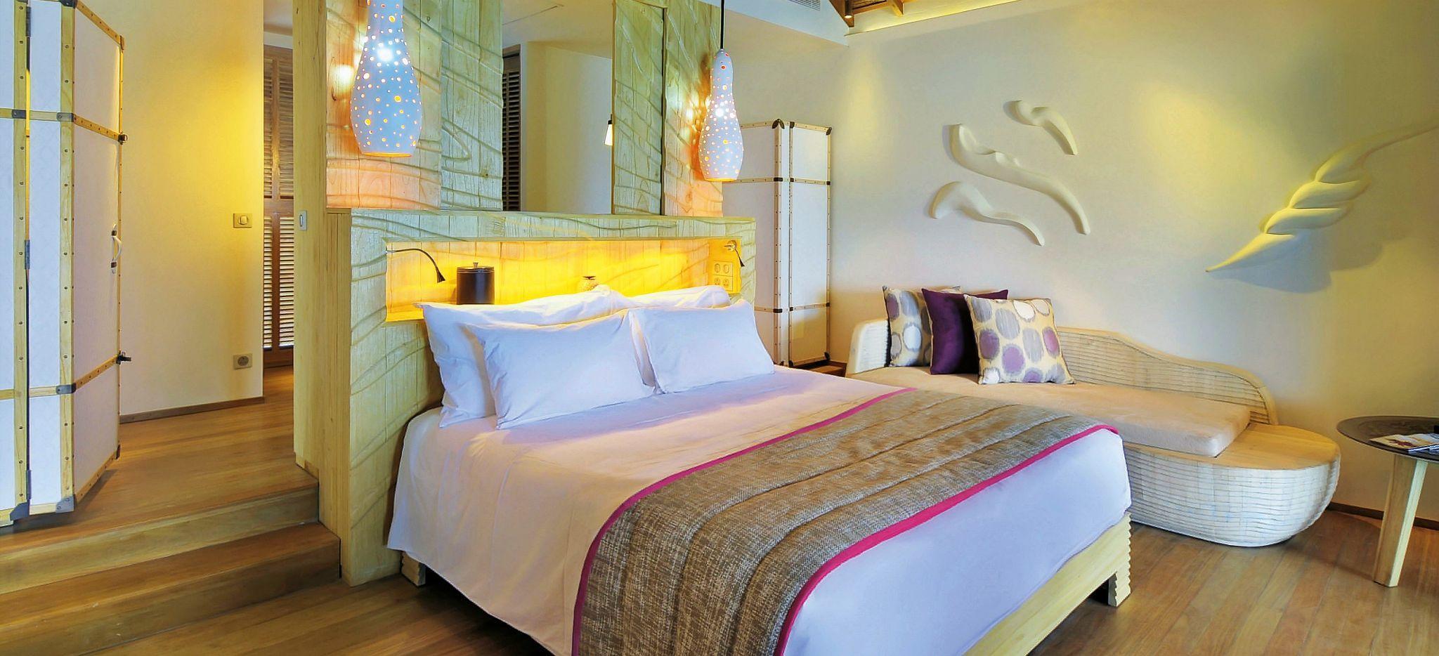 Ein luxuriöses Schlafzimmer eine Wasservilla des Hotels Constance Moofushi auf den Malediven