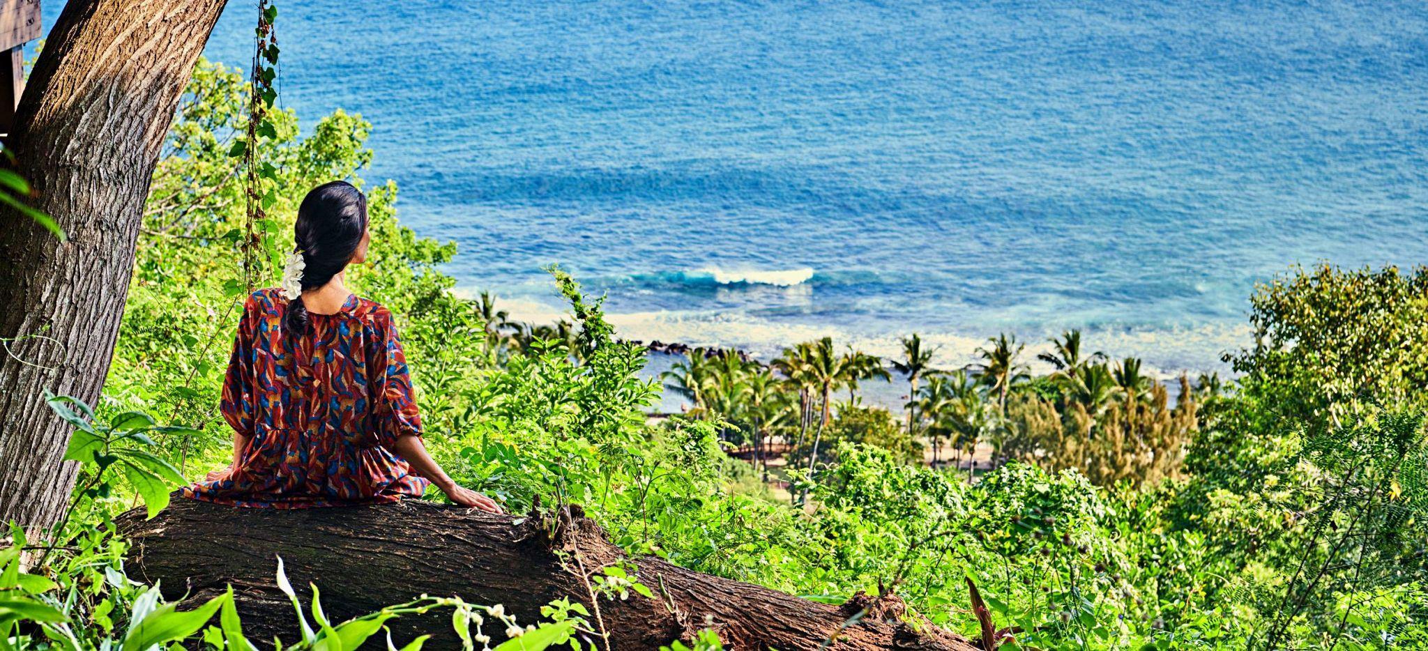 Eine Frau blickt von einem Baumstamm im Hotel Palm aus aufs Meer hinab