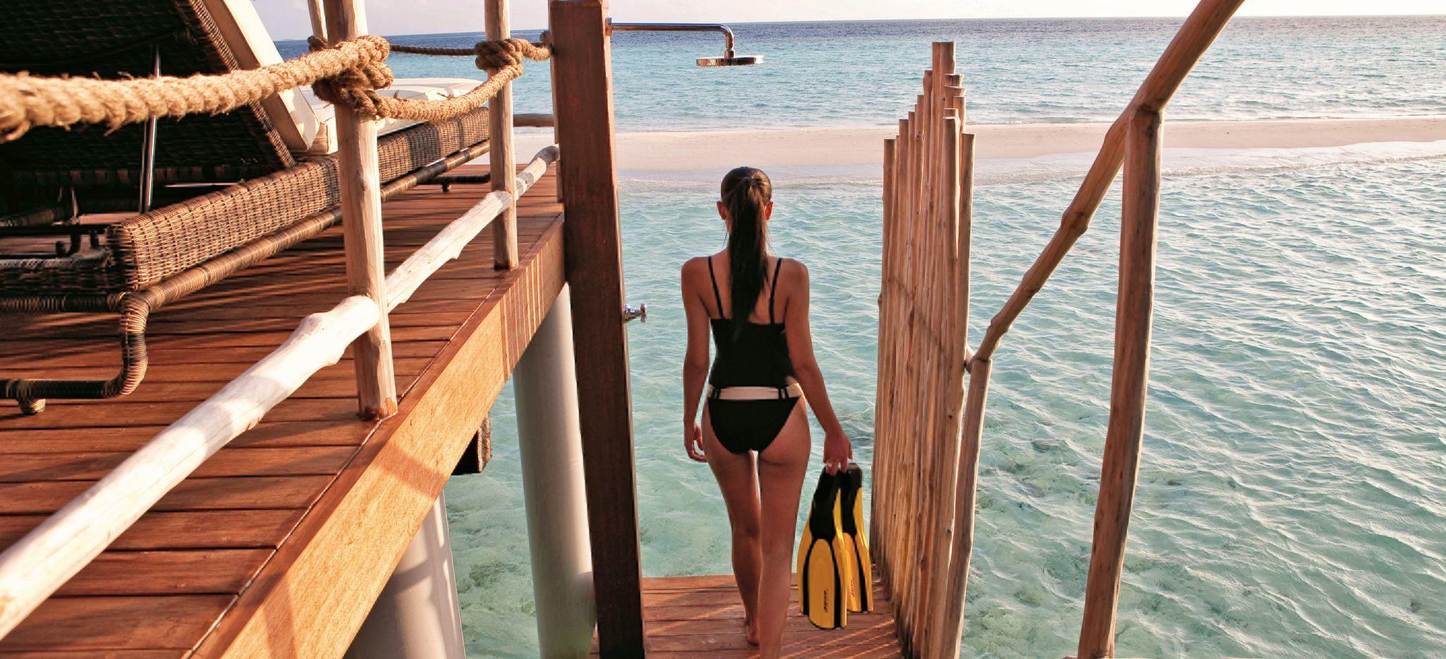 Eine Frau geht mit Schnorchel-Equipment über den Meerzugang einer Wasservilla in das Meer der Malediven
